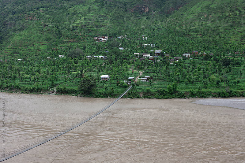 A suspension bridge leading to a village in Nepal. by Shikhar Bhattarai for Stocksy United