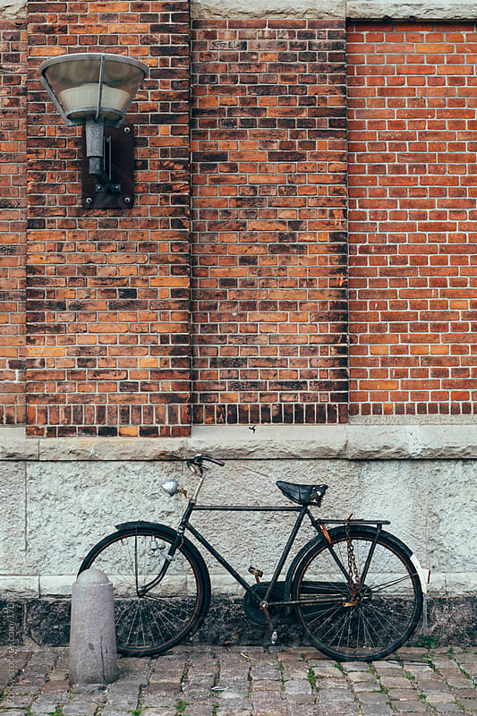 Old black bicycle leaning against red wall by Zocky for Stocksy United