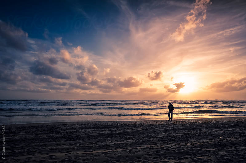 Man on the beach at sunset by GIC for Stocksy United