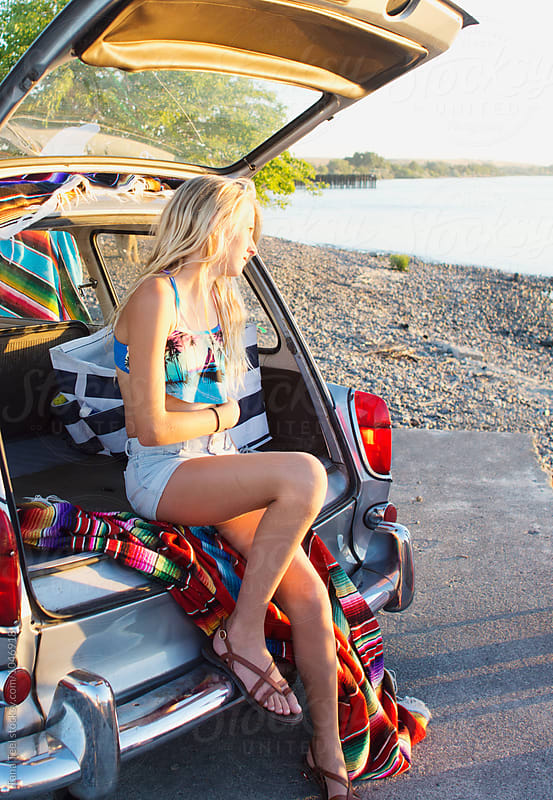 young girl sits in hatchback watching setting sun by Tana Teel for Stocksy United