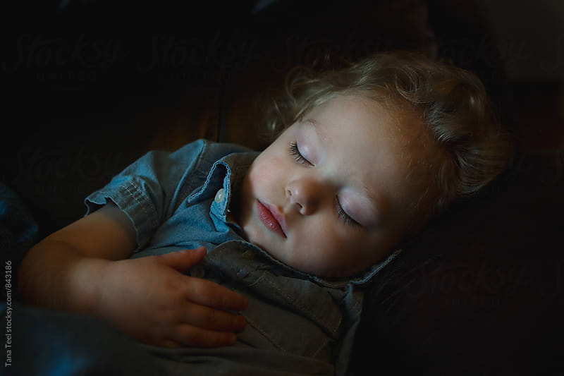 young boy sleeping on couch by Tana Teel for Stocksy United