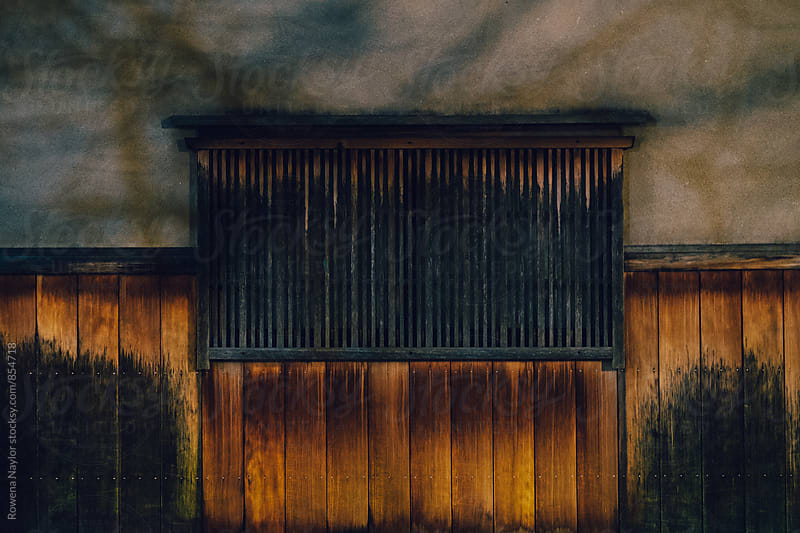 Detail of bettina of Japanese wooden shutters at night by Rowena Naylor for Stocksy United