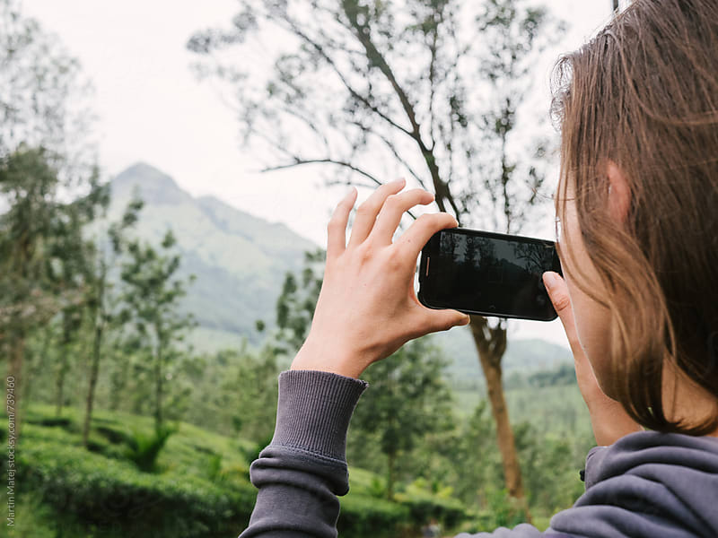 Girl taking a photo of Chembra Peak above tea plantations by Martin Matej for Stocksy United
