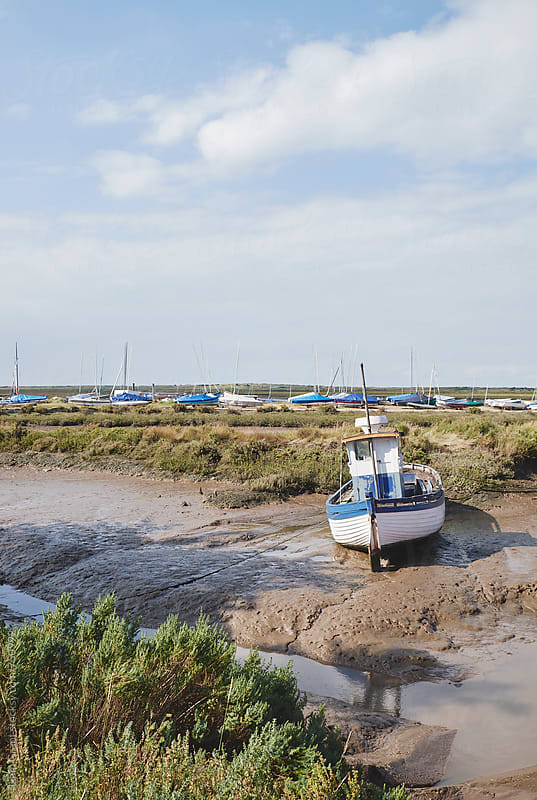 Fishing boat at low tide. Brancaster Staithe, Norfolk, UK. by Liam Grant for Stocksy United