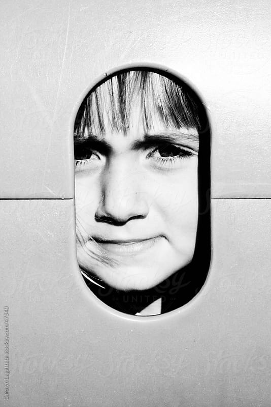 Child's face in a cut out peeking out of a play structure at the park by Carolyn Lagattuta for Stocksy United