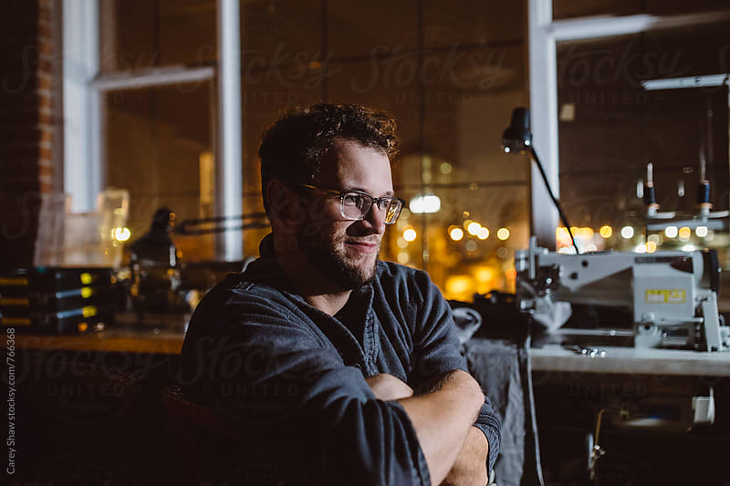 Evening portrait of man sitting in studio  by Carey Shaw for Stocksy United