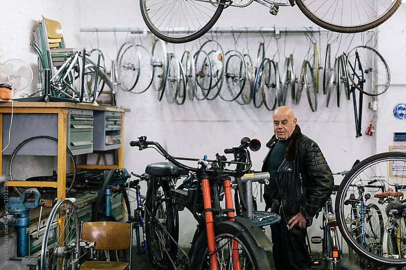 Senior Biker in workshop by VegterFoto for Stocksy United