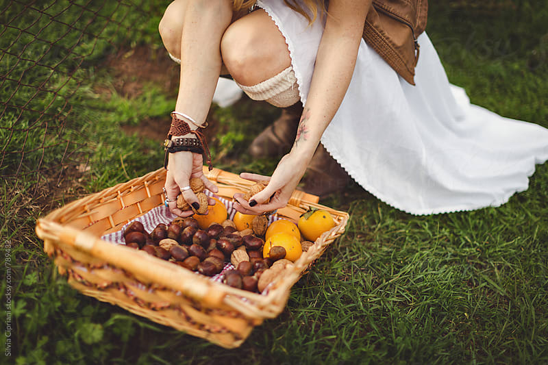 Woman gathering fresh fruit in a basket by Silvia Cipriani for Stocksy United