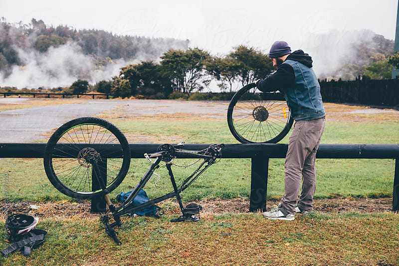 Man fixing his bike in a rainy weather by Andrey Pavlov for Stocksy United
