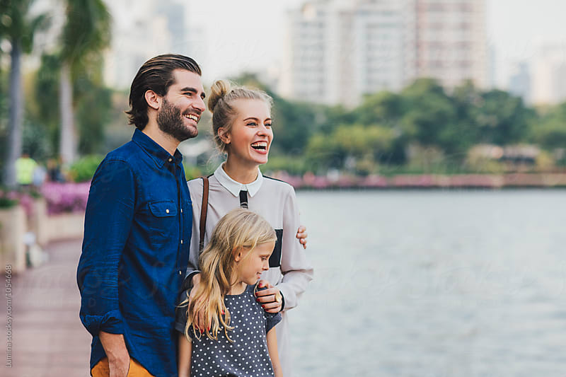 Family Standing Together and Smiling by Lumina for Stocksy United
