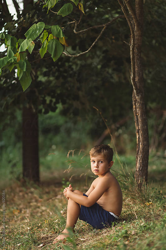 Boy sitting in nature. by Dejan Ristovski for Stocksy United