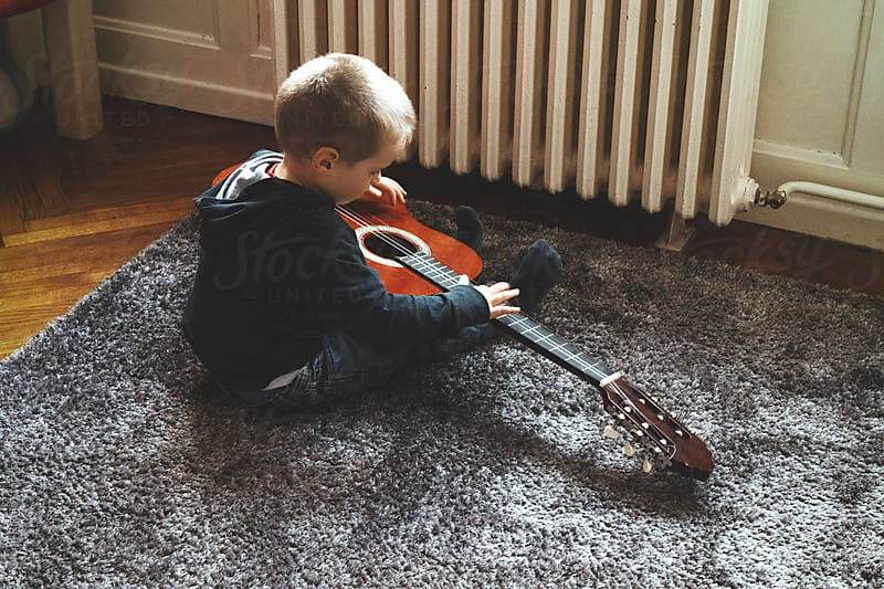 Cute little boy playing guitar in his room by Jovana Rikalo for Stocksy United