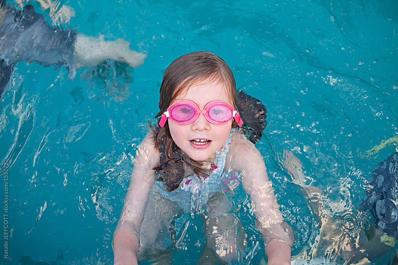 young girl holds on to the edge of a swimming pool playing by Natalie JEFFCOTT for Stocksy United