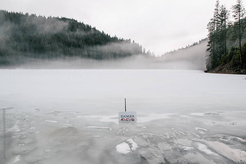 Danger sign on a frozen lake by Justin Mullet for Stocksy United