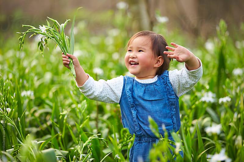 happy little asian girl in spring field by Bo Bo for Stocksy United