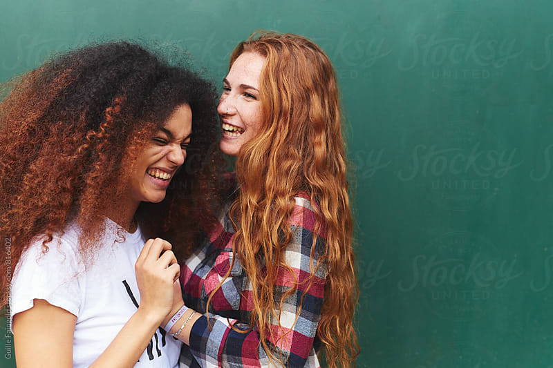 Two young women laughing together by Guille Faingold for Stocksy United