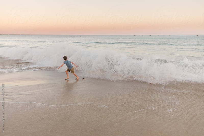 Child on the beach runs away from large waves by Rebecca Spencer for Stocksy United