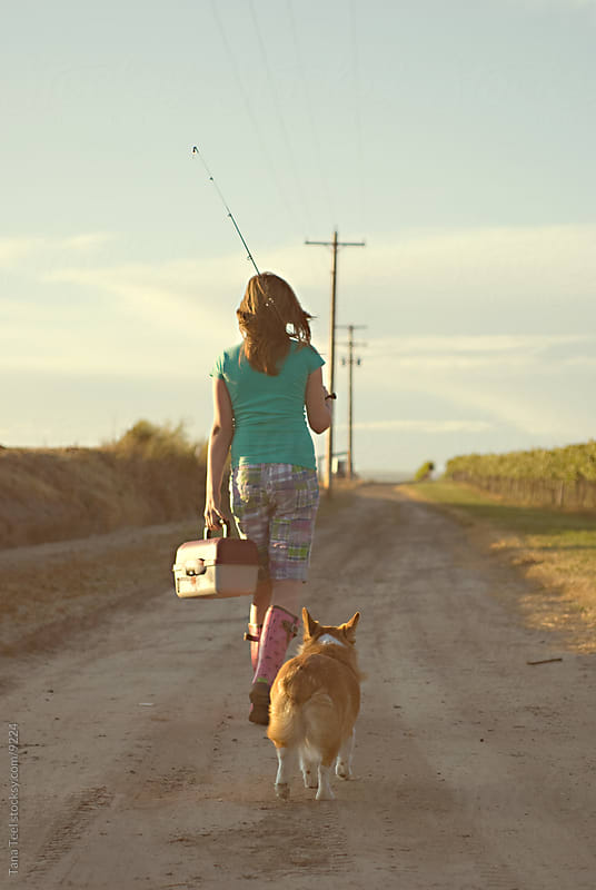 A young girl going fishing with her dog walking on a dirt road.  by Tana Teel for Stocksy United