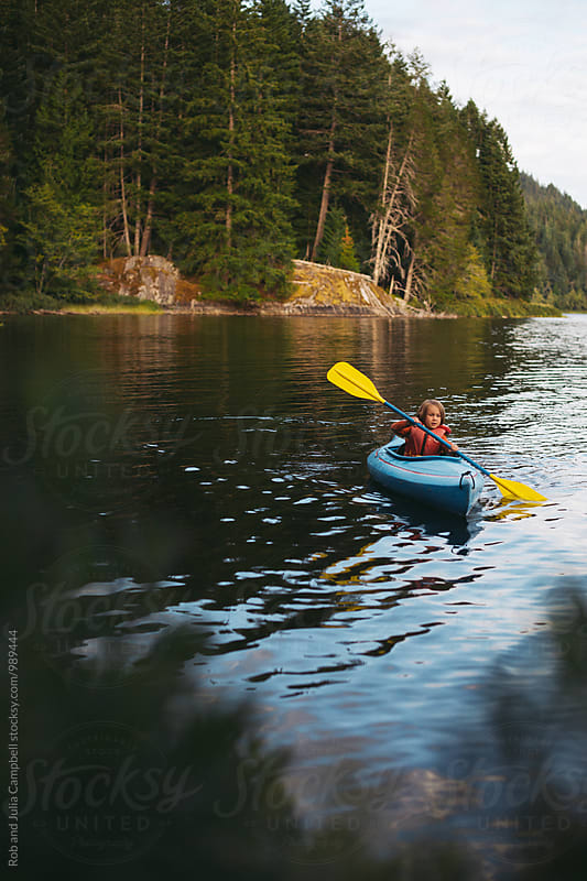 Young caucasian boy enjoying kayak on lake in summer by Rob and Julia Campbell for Stocksy United