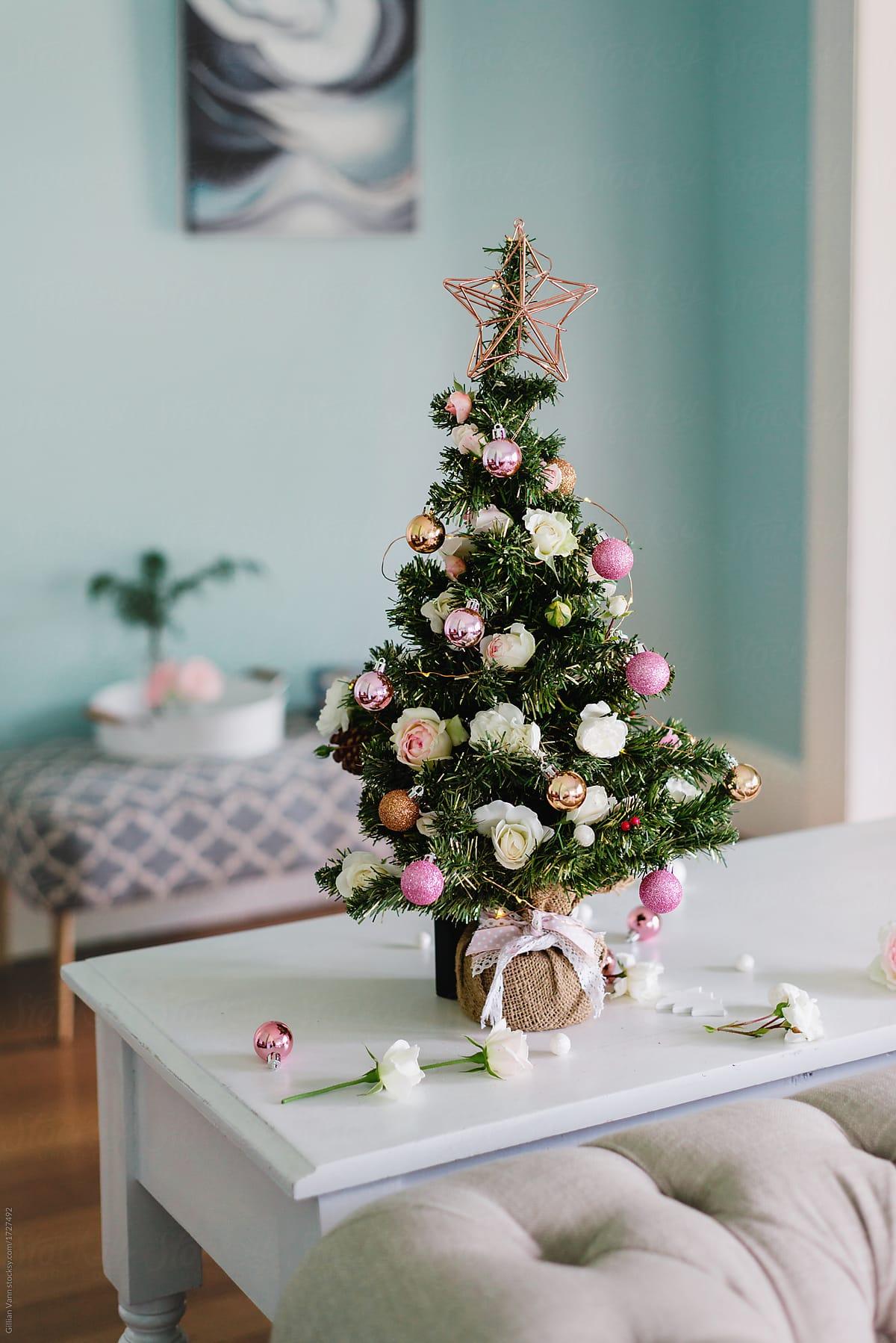 Small xmas tree on sofa tablein living room stocksy united - Where to put christmas tree in small living room ...