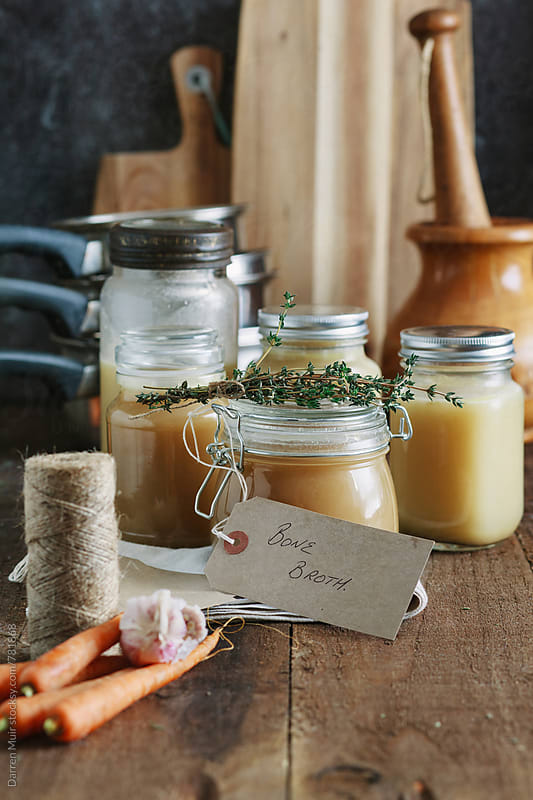 Bone broth in glass jars on a wooden table. by Darren Muir for Stocksy United