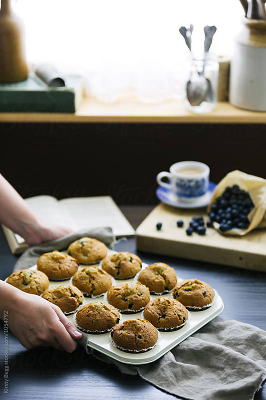 Woman sets down a tray of blueberry muffins on kitchen table by Kirsty Begg for Stocksy United