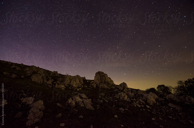 Starry night over the rocks at the mountain side by Cosma Andrei for Stocksy United