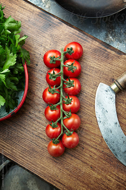 Cherry tomatoes on a wooden chopping board by James Ross for Stocksy United