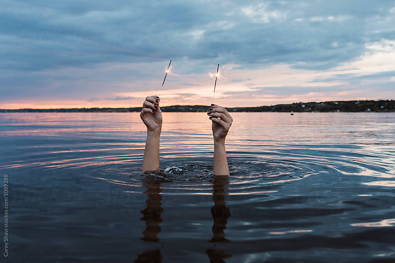 Person underwater holding two sparklers  by Carey Shaw for Stocksy United