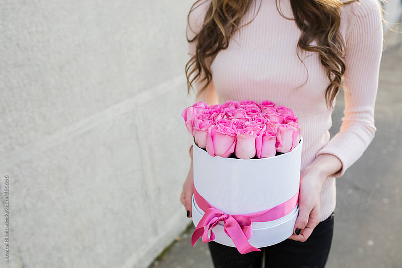 Young woman holding a box full of pink roses by Jovana Rikalo for Stocksy United