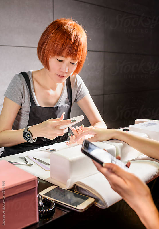 Young woman having manicure process of cosmetic procedure by Lawren Lu for Stocksy United