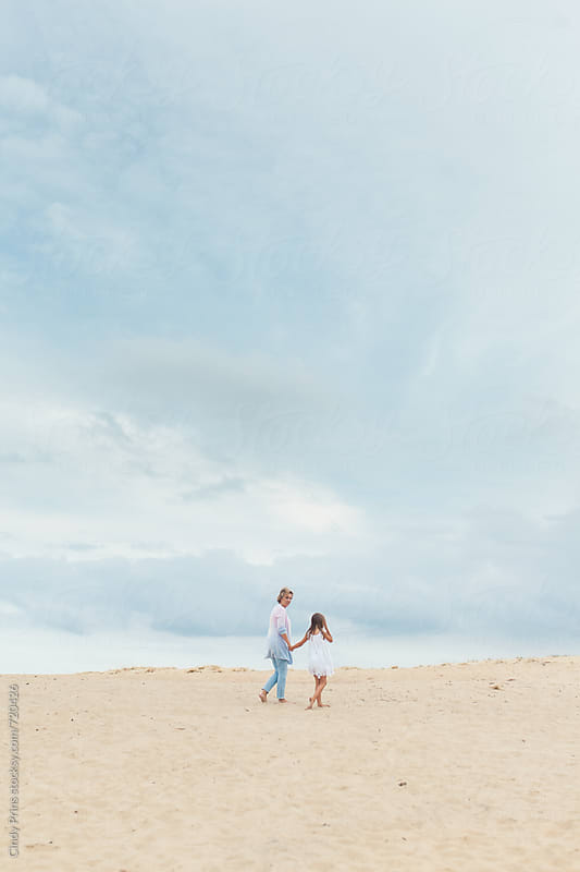 Grandmother and her granddaughter walking in the sand underneath a big sky by Cindy Prins for Stocksy United