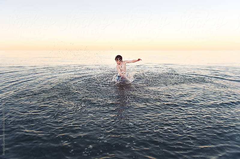 Spinning and splashing in calm water at the beach by Angela Lumsden for Stocksy United