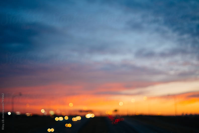A two way highway under a beautiful sunset sky, out of focus by Riley J.B. for Stocksy United