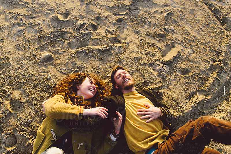 Young playful couple laying on the sand  by Evgenij Yulkin for Stocksy United