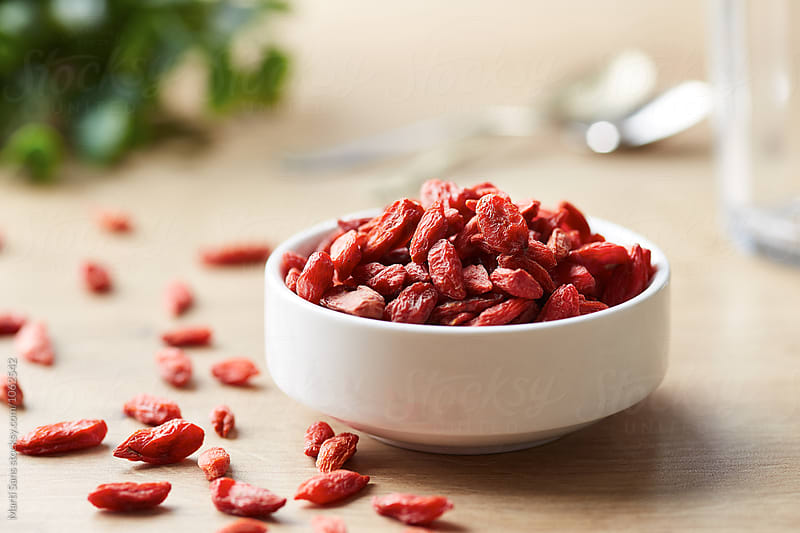 Bowl of goji berries with several scattered on table by Martí Sans for Stocksy United