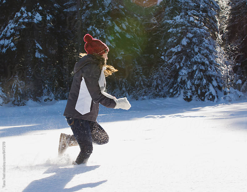 young woman runs through deep snow by Tana Teel for Stocksy United