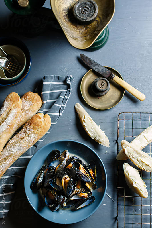 Moules mariniere served with crusty french bread. by Darren Muir for Stocksy United