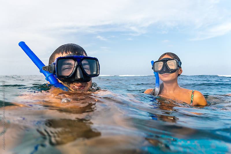 Couple in masks and snorkels having fun in water by Alejandro Moreno de Carlos for Stocksy United