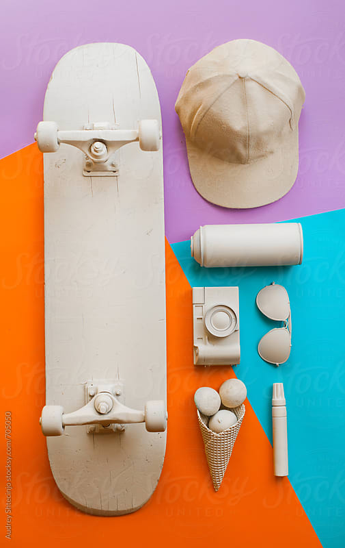 Various arranged skateboarder/teenager objects  on blue orange and purple background. by Audrey Shtecinjo for Stocksy United