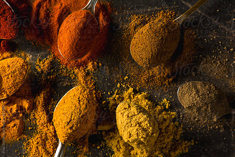 Colorful spices on dark background by Pixel Stories for Stocksy United