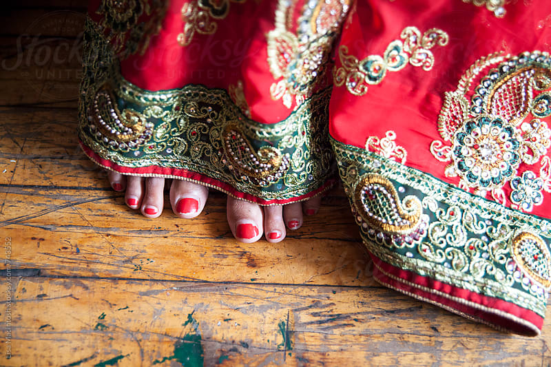 painted red toes peeking out from under traditional saree by Lisa MacIntosh for Stocksy United