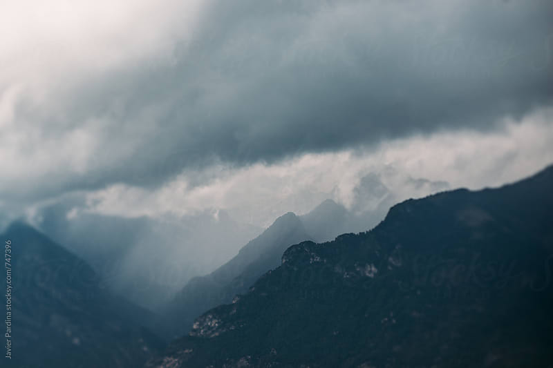 storm clouds on the mountain top by Javier Pardina for Stocksy United