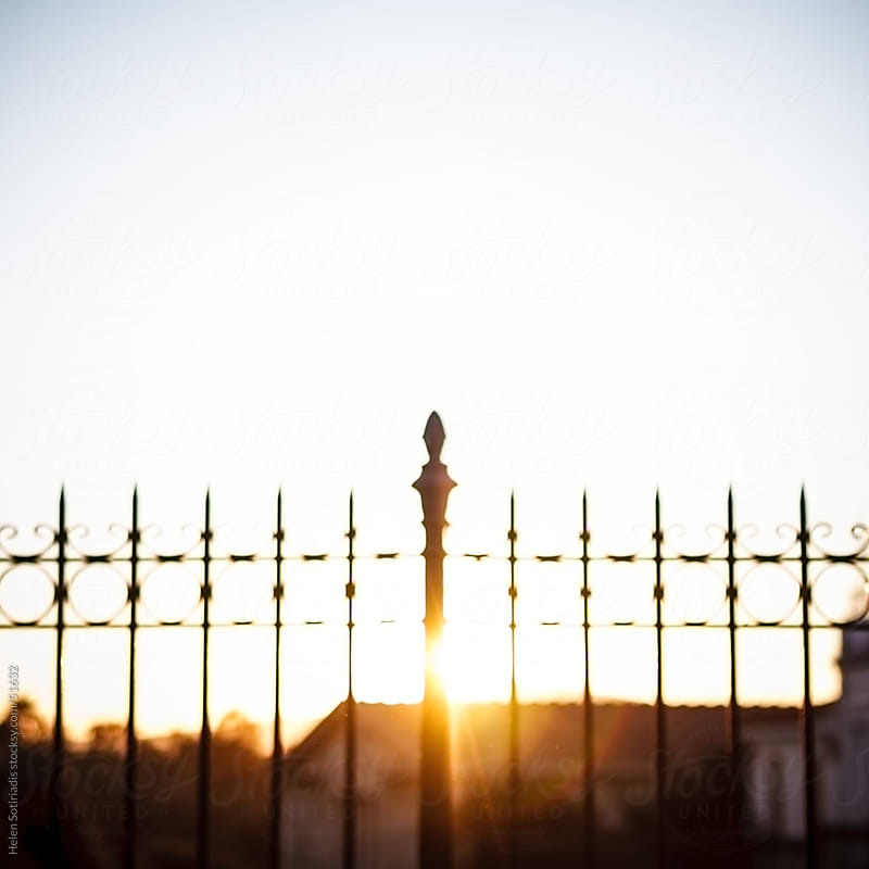 A fence that is backlit by the sun by Helen Sotiriadis for Stocksy United