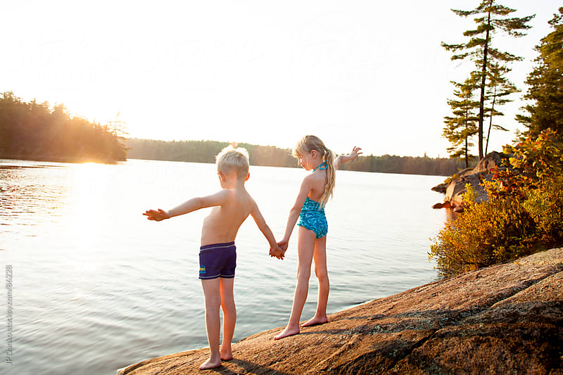 Little Girl and Boy Swimming at Lake With Summer Sunset by JP Danko for Stocksy United