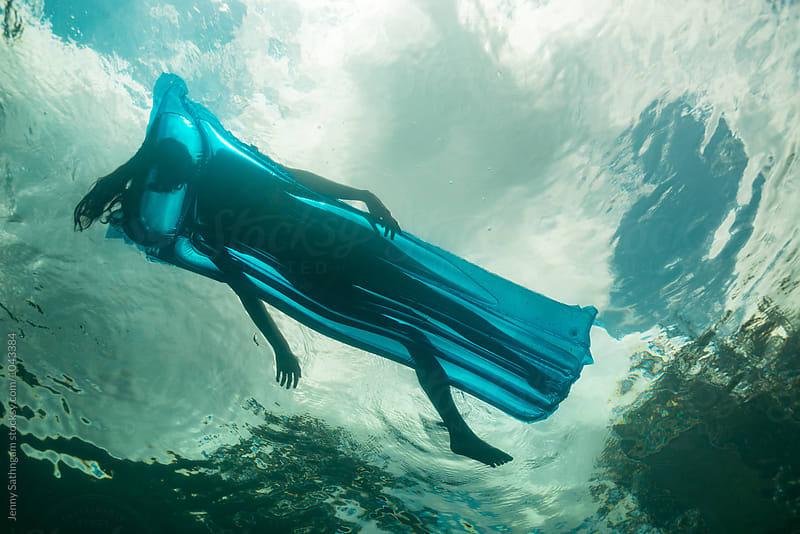 Underwater photo of a beautiful young woman swimming with a float by Jenny Sathngam for Stocksy United