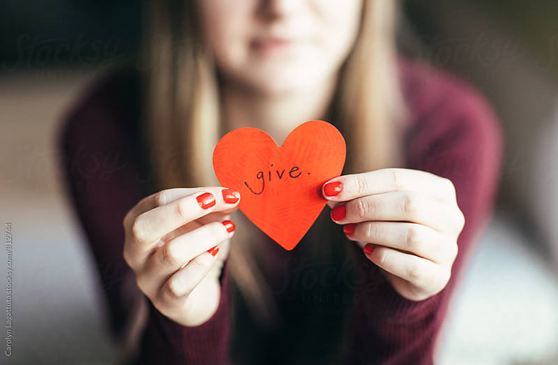 Female holding a red paper heart with the word Give written on it by Carolyn Lagattuta for Stocksy United