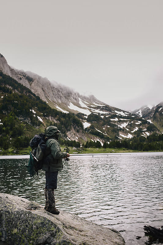 Lake fishing in the mountain in a stormy day by Miquel Llonch for Stocksy United