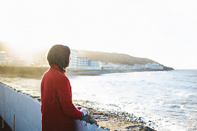 Woman standing behind sea wall looking out to sea by Suzi Marshall for Stocksy United