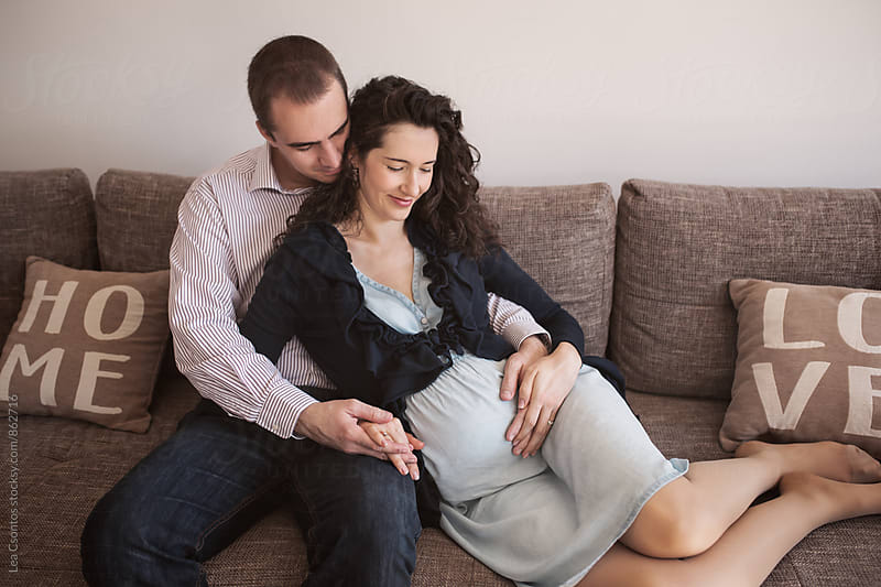 A beautiful pregnant woman snuggling on a sofa with her husband.  by Lea Csontos for Stocksy United